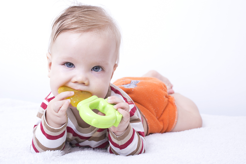 Baby boy playing with teether, chewing toy